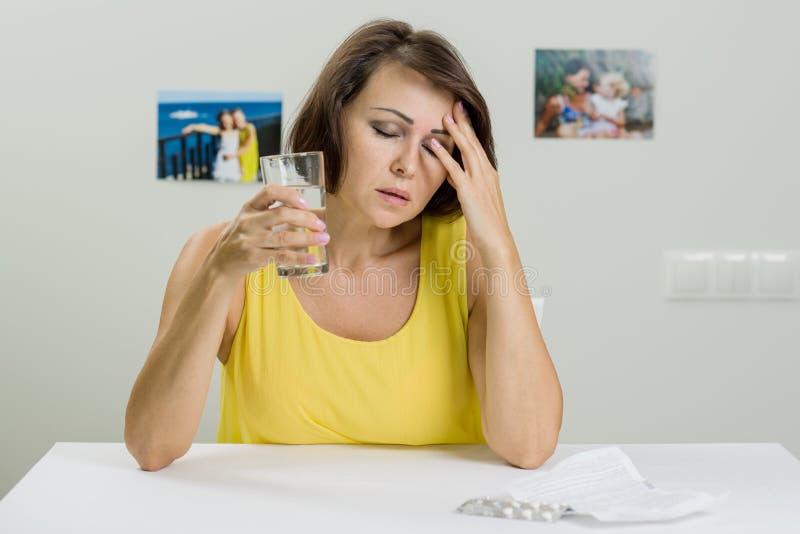 Dojrzała kobieta z pigułkami i szkło woda w domu zdjęcia stock
