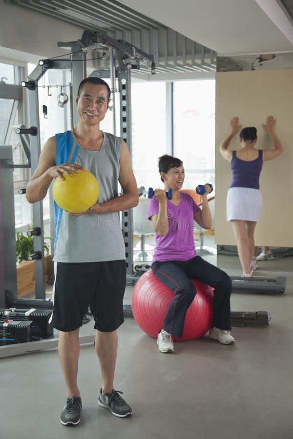 Dojrzała mężczyzna mienia piłka w gym, ludzie ćwiczy na tle obraz royalty free