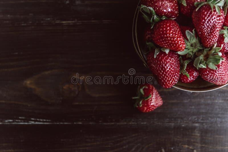 Dojrzała organicznie truskawka na drewnianym tle w nieociosanym stylu fotografia royalty free
