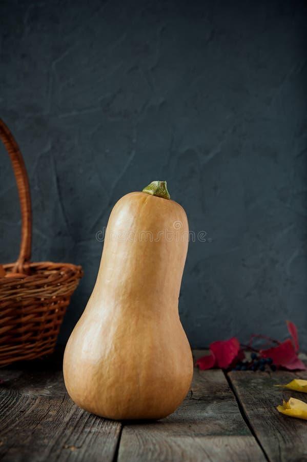 Dojrzała pomarańczowa bania stading na nieociosanym drewnianym stole na ciemnym kamiennym tle Jarosz, jesieni żniwo, dziękczynien obrazy royalty free