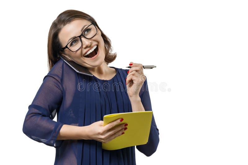 Dojrzała uśmiechnięta kobieta opowiada na telefonie z notatnikiem i piórze w ręce, kobieta pisze w notatniku Biały tło odizolowyw obraz stock