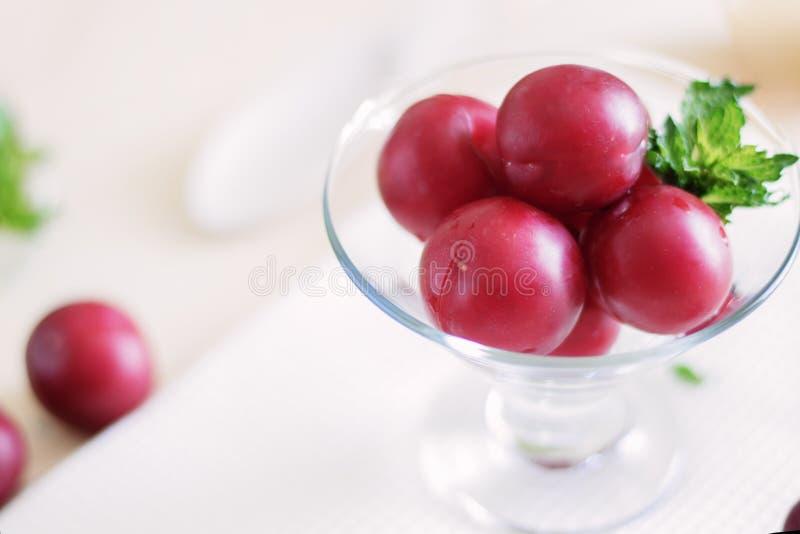 Dojrzałe śliwki w górę słuzyć z mennicą w szklanej śmietance na tle rocznika drewniany stół, zdrowi foods, żywienioniowe owoc a zdjęcie stock