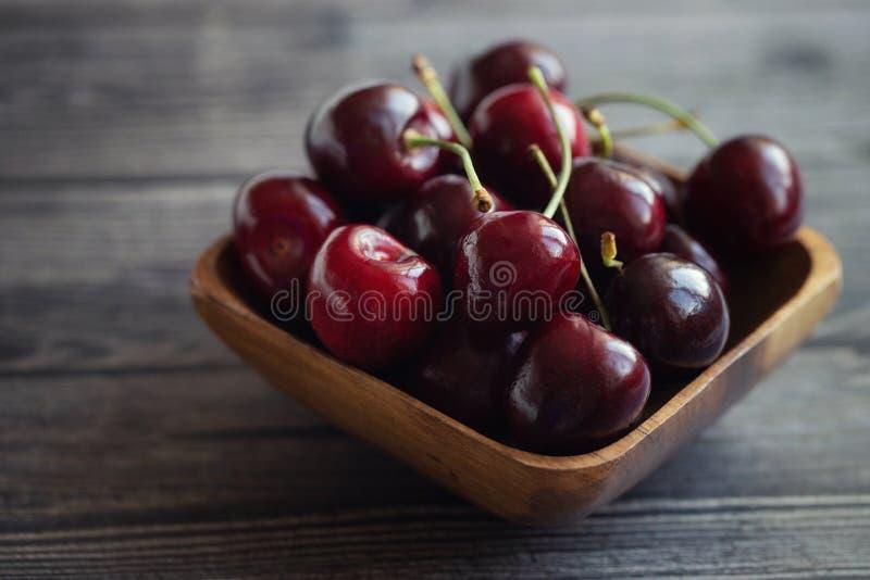 Dojrzałe świeże wiśnie w drewnianym pucharze knedle t?a jedzenie mi?sa bardzo wiele Czerwona soczysta czereśniowa jagoda na popie zdjęcie royalty free