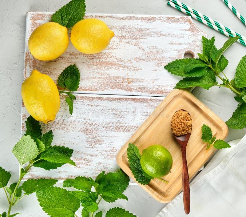 dojrzałe żółte całe cytryny, wapno, brązu cukier i wiązka świeża mennica, zdjęcie royalty free