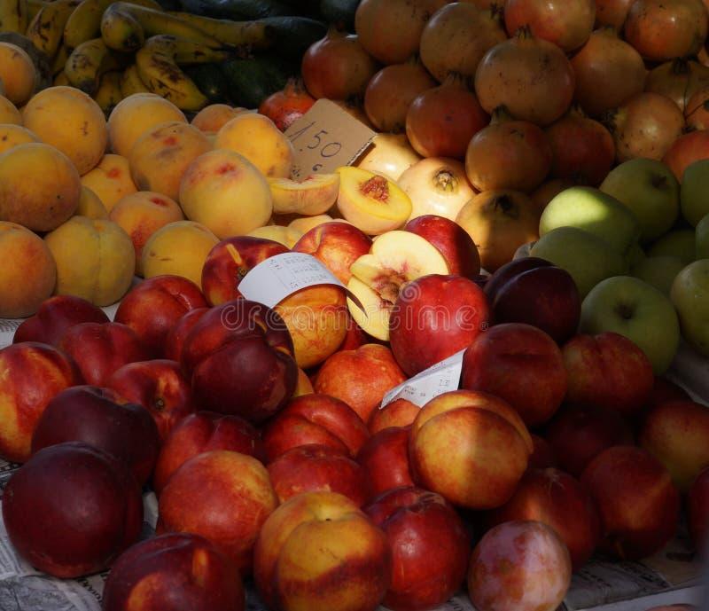 Dojrzałe brzoskwinie i nektaryny iluminują zasolonego promień w owocowym rynku zdjęcia royalty free