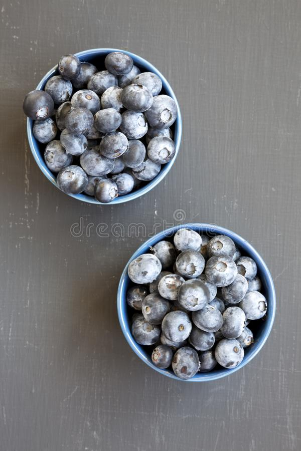Dojrzałe organicznie czarne jagody w błękitnych pucharach nad czerni powierzchnią, odgórny widok Lato jagoda Mieszkanie nieatutow zdjęcie stock