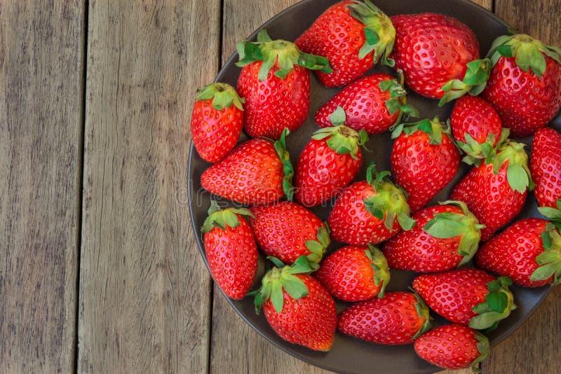 Dojrzałe organicznie truskawki na zmroku talerzu na deski drewnianym tle, zamykają up, zdrowy jedzenie, detox zdjęcia stock