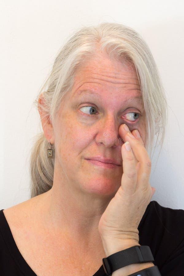 Dojrzałego kobiety ciągnięcia puszka niska powieka, patrzeje popierać kogoś, naturalna żadny makeup, neutralny tło obrazy royalty free