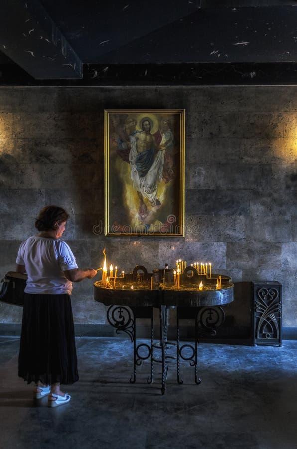 Dojrzałej kobiety oświetleniowe świeczki w Armeńskim kościół chrześcijańskim z Chrześcijański metaforyka na ścianie obrazy stock