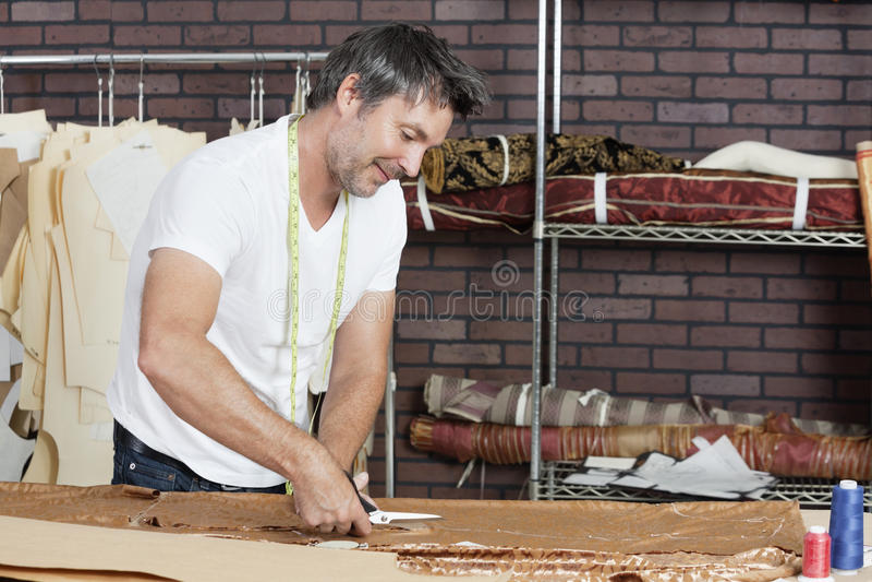 Dojrzałej męskiej krawcowej tnąca tkanina w projekta studiu obrazy royalty free