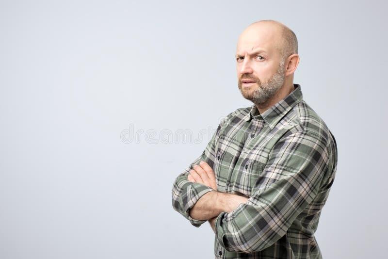 Dojrzały łysy mężczyzna w w kratkę koszulowej pozyci z rękami krzyżować przy kamerą i poważną twarzą, patrzeje podejrzany obraz stock