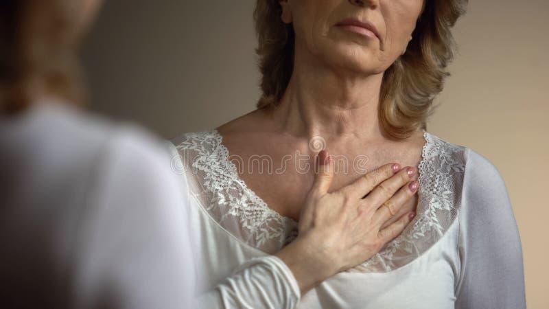 Dojrzały żeński macanie jej marszcząca szyja przed lustrem, starzenie się proces zdjęcia royalty free