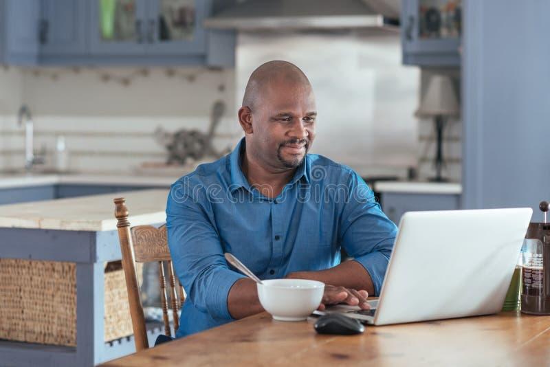 Dojrzały Afrykański mężczyzna wyszukuje online z laptopem nad śniadaniem zdjęcia royalty free