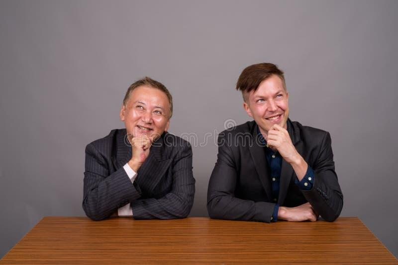Dojrzały Azjatycki biznesmen i młody Kaukaski biznesmena główkowanie zdjęcie royalty free