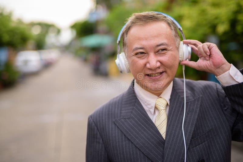 Dojrzały Azjatycki biznesmen słucha muzyka w ulicach przewyższa zdjęcie stock