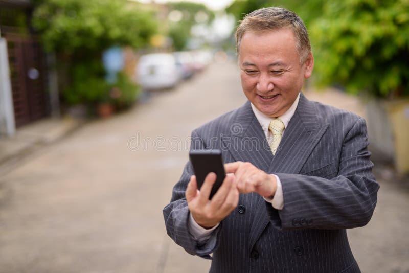 Dojrzały Azjatycki biznesmen używa telefon komórkowego w ulicach przewyższa zdjęcia stock