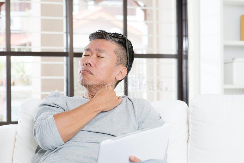Dojrzały Azjatycki mężczyzna ramienia ból podczas gdy używać pastylka komputer obraz royalty free
