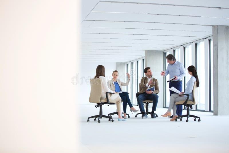 Dojrzały biznesmen dyskutuje z drużynowym obsiadaniem na krześle w nowym biurze obraz stock