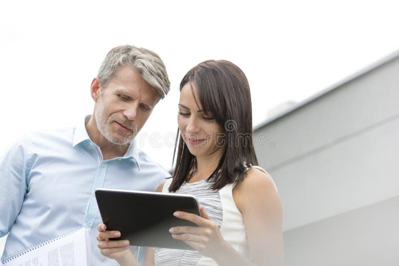 Dojrzały biznesmen dyskutuje z kolegą nad cyfrową pastylką przy tarasem w biurze fotografia royalty free