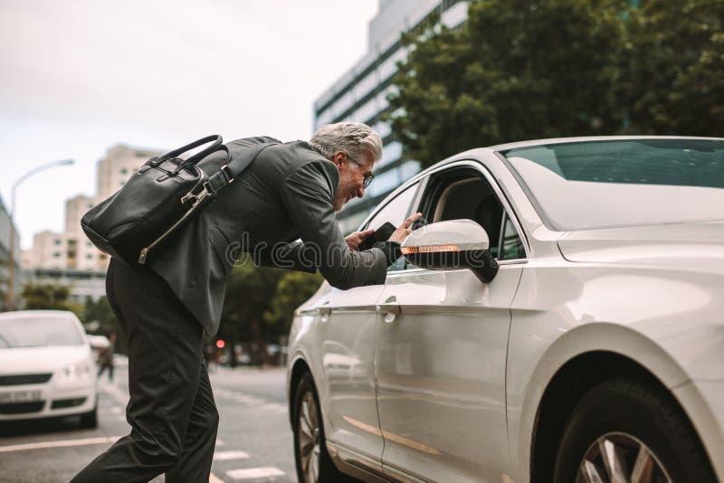 Dojrzały biznesmen opowiada taksówkarz zdjęcia stock