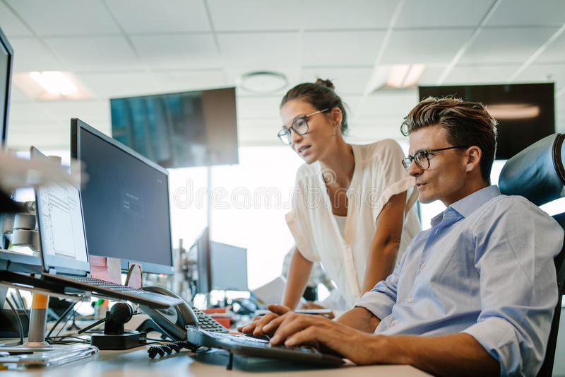 Dojrzały biznesmen pracuje na komputerze z kolegą zdjęcia royalty free