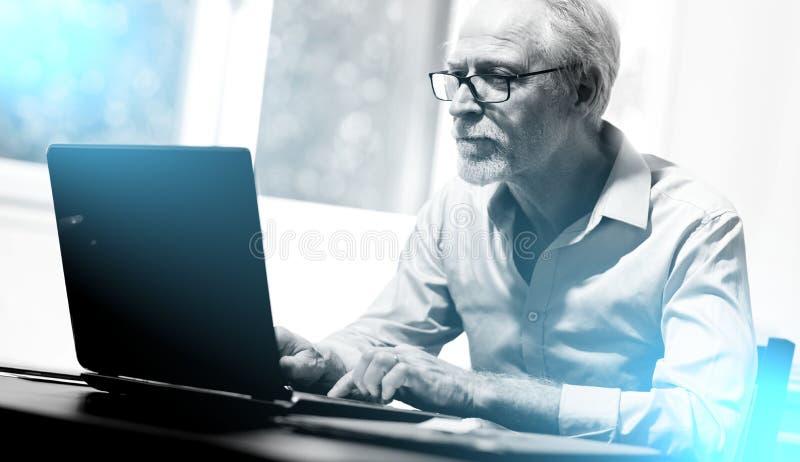 Dojrzały biznesmen pracuje na laptopie; lekki skutek zdjęcia stock