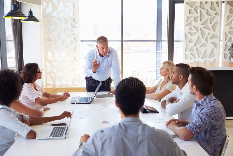 Dojrzały biznesmen przedstawia koledzy przy spotkaniem zdjęcie stock