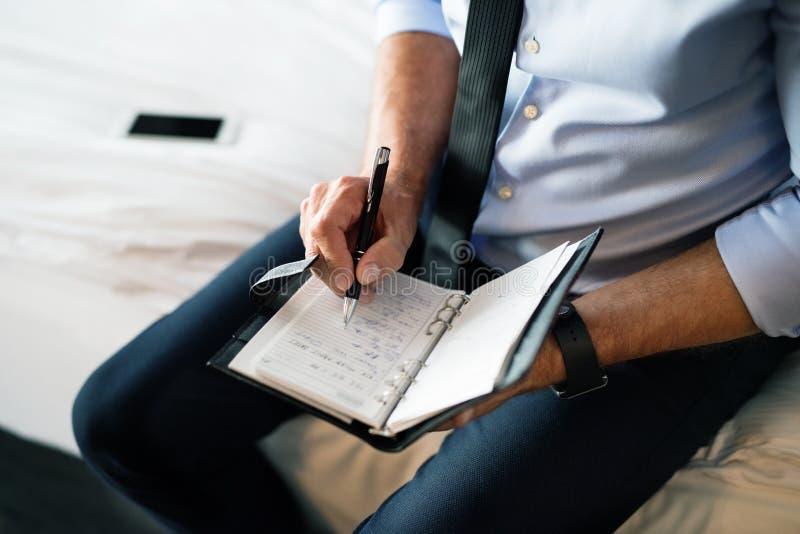 Dojrzały biznesmen robi notatkom w pokoju hotelowym zdjęcia stock