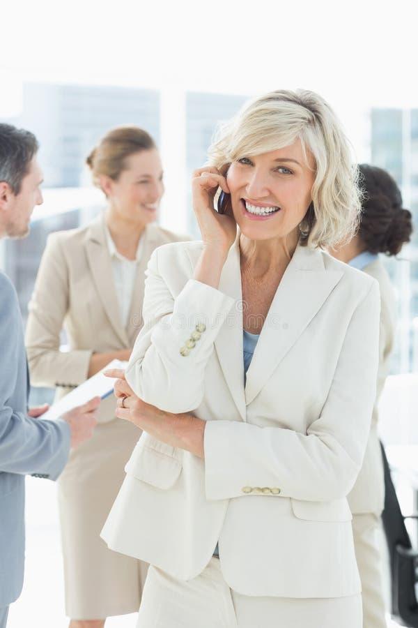 Dojrzały bizneswoman na wezwaniu z kolegami dyskutuje przy biurem zdjęcie royalty free