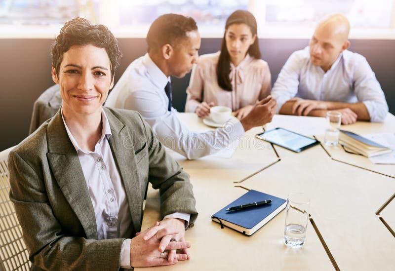 Dojrzały bizneswoman patrzeje kamerę podczas biznesowego spotkania obraz royalty free