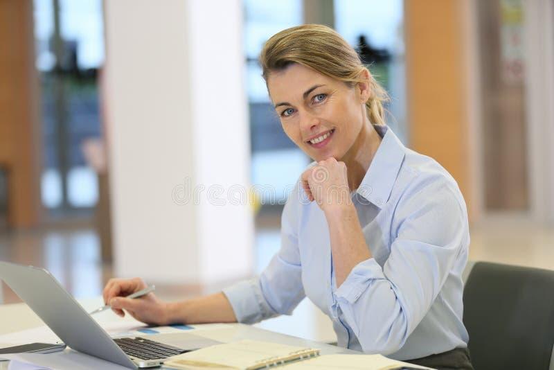 Dojrzały bizneswoman pracuje przy biurem fotografia royalty free