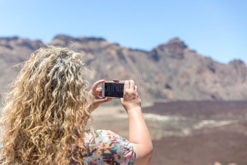 Dojrzały blondynka turysta bierze obrazki pustynia powulkaniczny krajobraz i, Tenerife wyspa fotografia stock