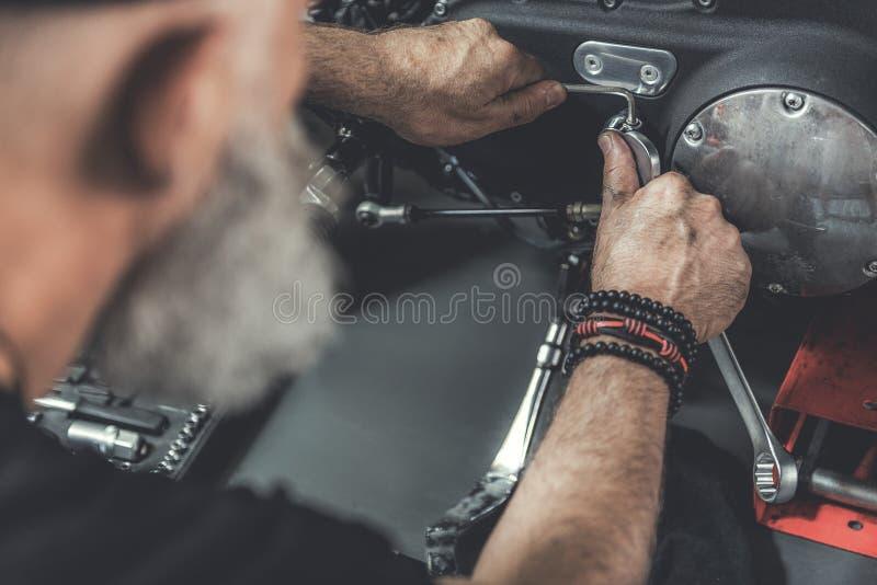 Dojrzały brodaty mężczyzna robi odświeżaniu motocykl zdjęcie stock
