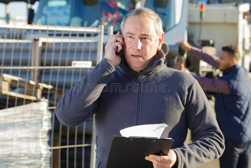 Dojrzały budowniczy z telefonicznym outside na pracy miejscu zdjęcie stock