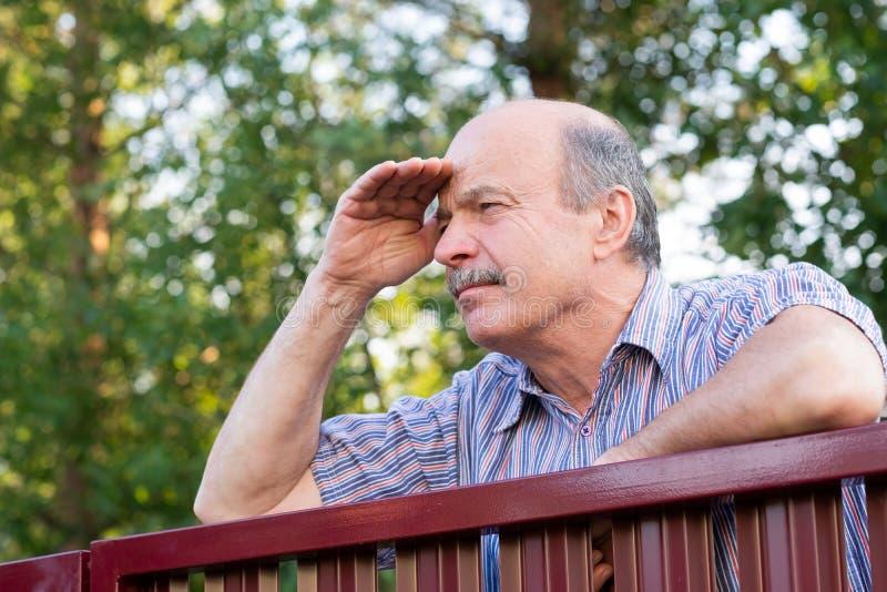Dojrzały caucasian mężczyzna ostrożnie ogląda nad ogrodzeniem zdjęcia royalty free
