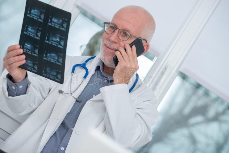 Dojrzały doktorski patrzeje promieniowanie rentgenowskie obrazek i używać telefon fotografia royalty free