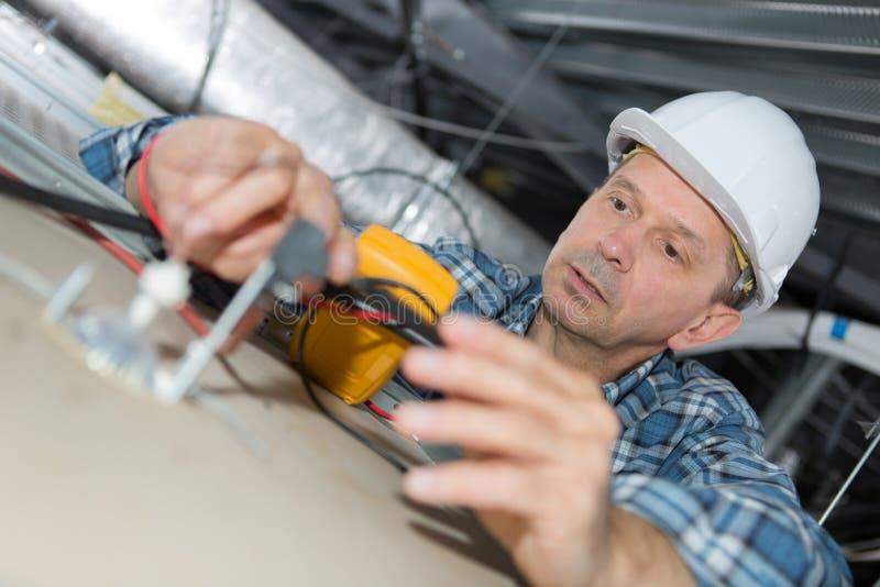 Dojrzały elektryk sprawdza budynek instalację elektryczną w suficie obraz stock