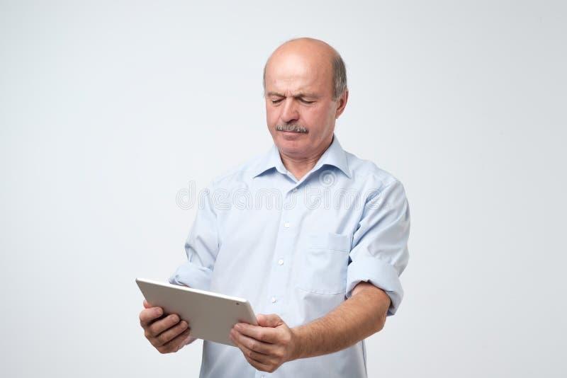 Dojrzały europejski mężczyzna używa cyfrową pastylkę Intryguje i wprawiać w zakłopotanie obrazy royalty free
