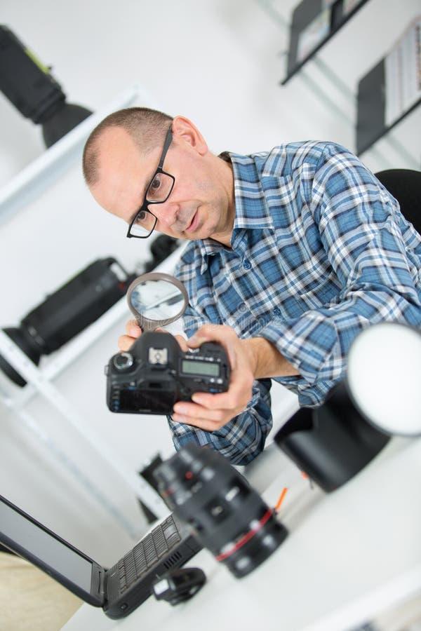 Dojrzały fotograf sprawdza kamerę z powiększać glas fotografia royalty free