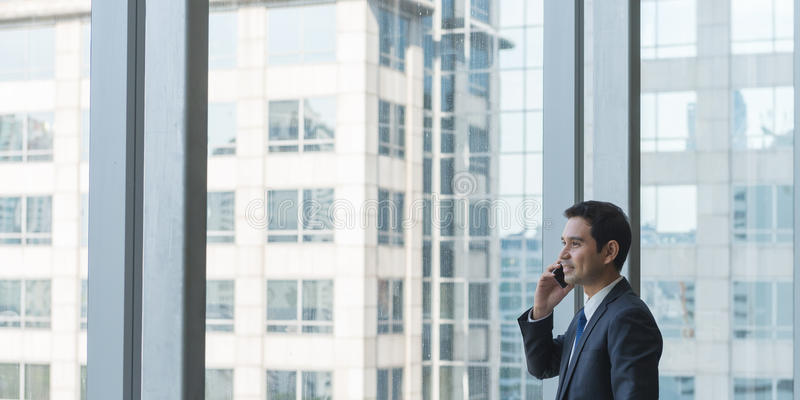 Dojrzały i ufny dyrektor wykonawczy patrzeje przyglądający z wielkich okno przy widokiem miasto below fotografia stock