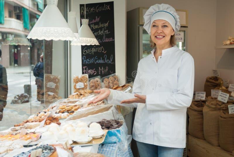 Dojrzały kobieta szef kuchni przy ciasteczko pokazem z ciastem obrazy stock