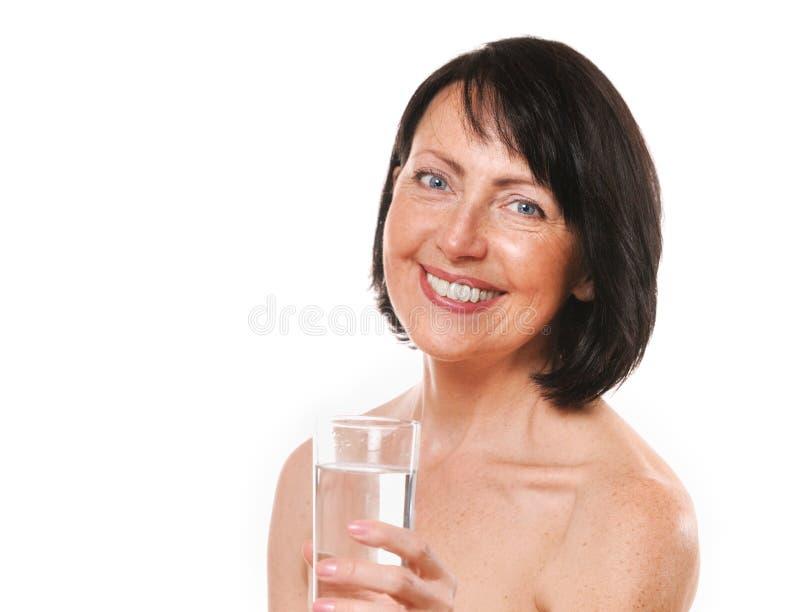 Dojrzały kobiety oferty szkło woda zdjęcia stock