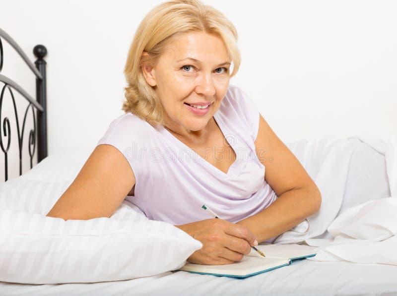 Dojrzały kobiety writing w dzienniczku fotografia stock