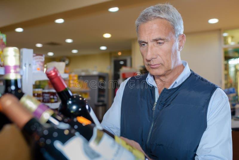 Dojrzały mężczyzna mienia butelki wino zdjęcie royalty free