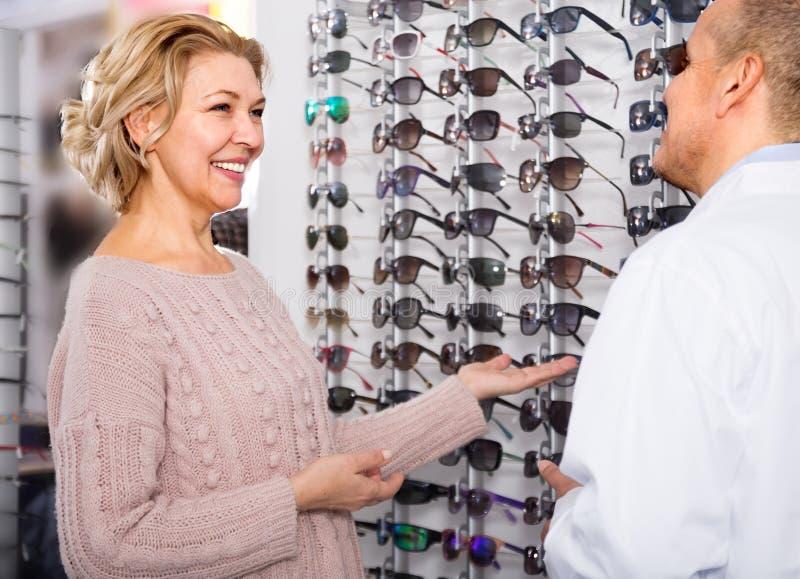 dojrzały mężczyzna okulisty klient doradza Dojrzałej blondynki blisko pokazów okularów przeciwsłonecznych obraz stock