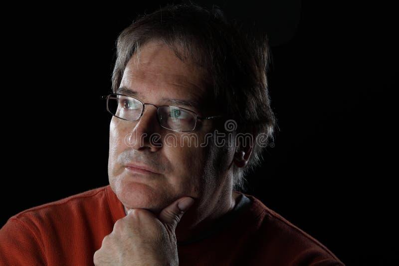 Dojrzały mężczyzna patrzeje quizzical - na czarnym tle obraz royalty free