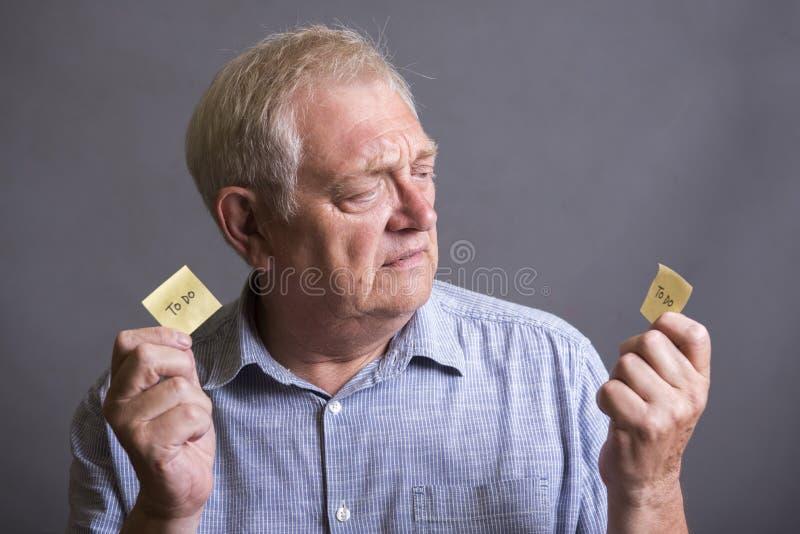 Dojrzały mężczyzna patrzeje robić liście pisać na nutowym papierze zdjęcie royalty free