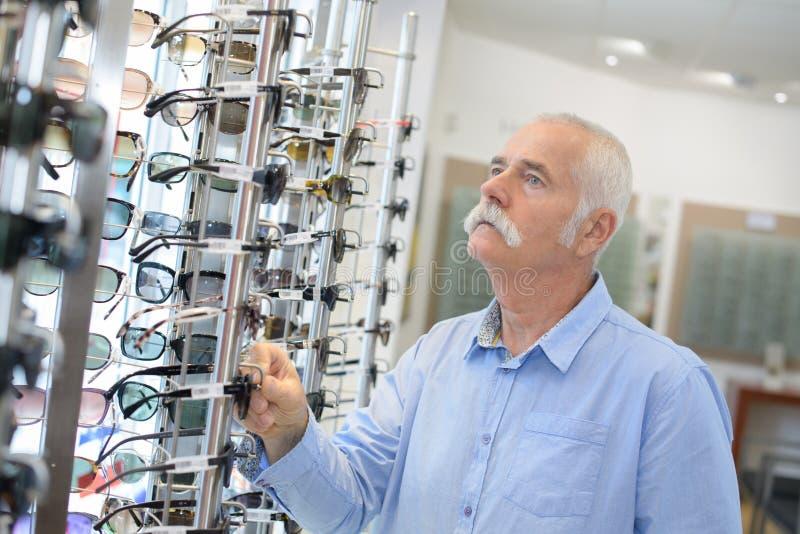 Dojrzały męski emeryt wybiera szkła w optyka sklepie zdjęcie royalty free