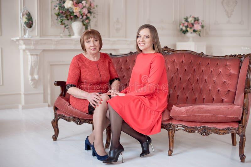 Dojrzały matki I córki mienie wręcza być usytuowanym przy stołem zdjęcia stock