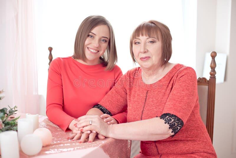 Dojrzały matki I córki mienie wręcza być usytuowanym przy stołem zdjęcie stock